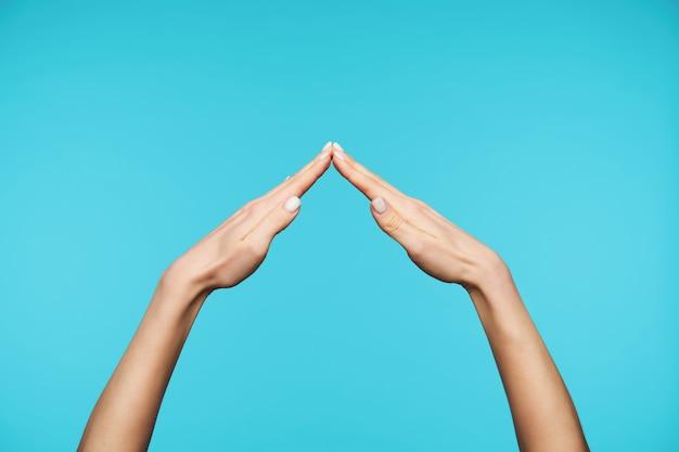 Feche as palmas dobráveis próximas uma da outra enquanto forma o telhado da placa da casa