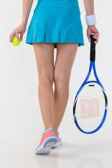 Feche as pernas da mulher jovem de tênis com uma raquete no fundo branco