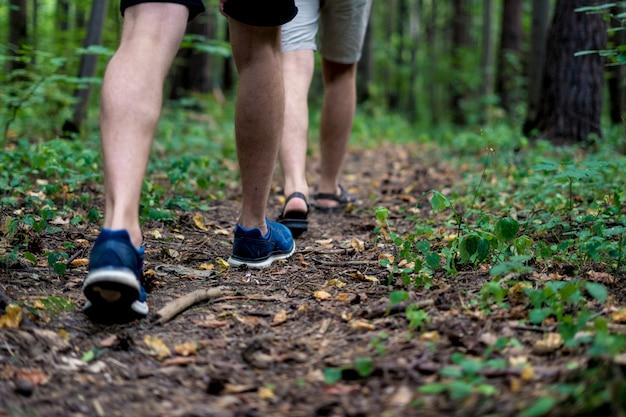 Feche as pernas de pessoas andando na floresta de outono em uma viagem de acampamento