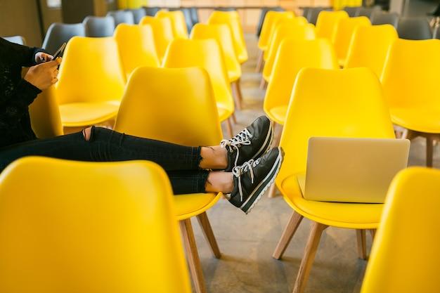Feche as pernas de uma jovem elegante sentada na sala de aula com o laptop, sala de aula com muitas cadeiras amarelas, tênis, tênis, tendência da moda