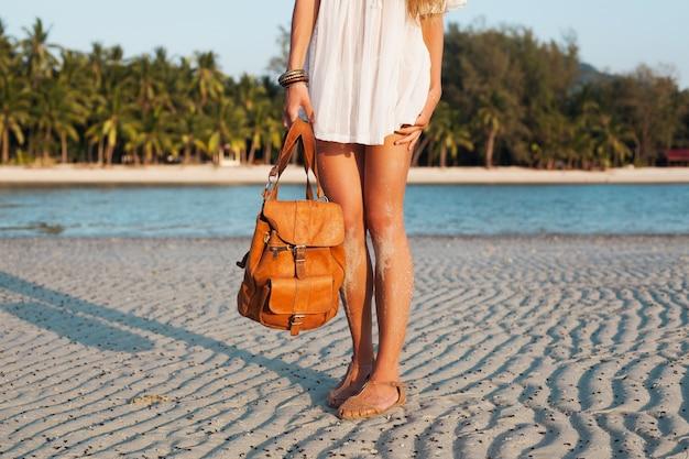 Feche as pernas de uma mulher com vestido de algodão branco caminhando em uma praia tropical segurando uma mochila de couro