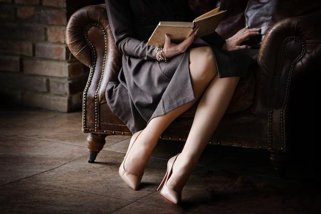 Feche as pernas de uma mulher sentada em uma cadeira de couro antiga lendo um livro