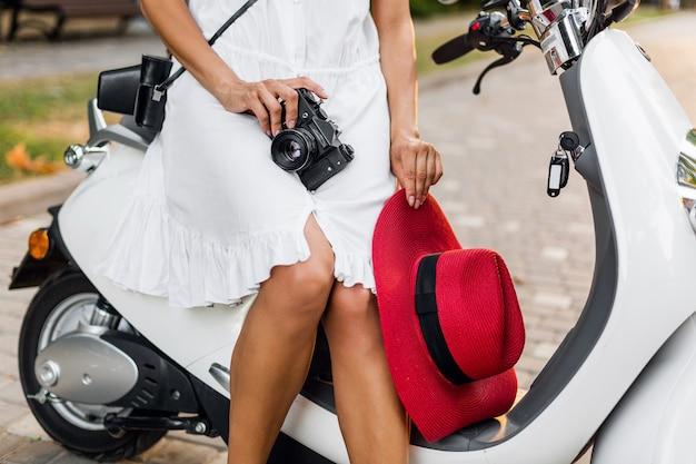 Feche as pernas de uma mulher sentada em uma motocicleta na rua, estilo férias de verão, viajando, roupas elegantes, aventuras, segurando uma câmera fotográfica vintage, chapéu de palha vermelho