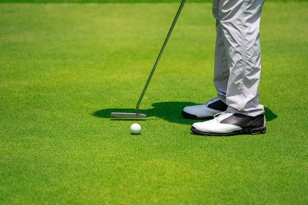 Feche as pernas do jogador de golfe e clube de golfe batendo bola para buraco no golfe verde