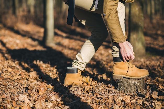 Feche as pernas em sapatos de rastreamento de homem moderno viajando na floresta de outono
