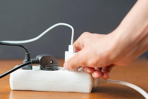 Feche as pessoas com a mão conecte a carga elétrica na tomada d