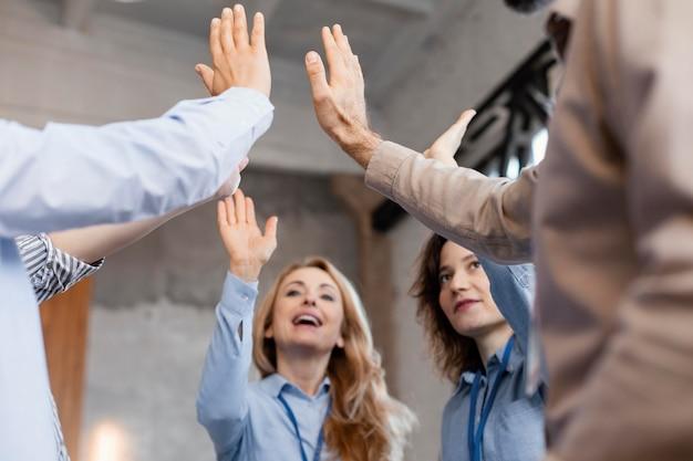 Feche as pessoas com as mãos levantadas