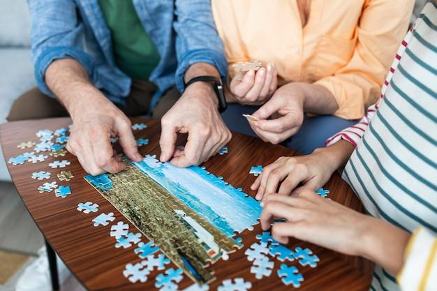 Feche as pessoas fazendo quebra-cabeças juntas