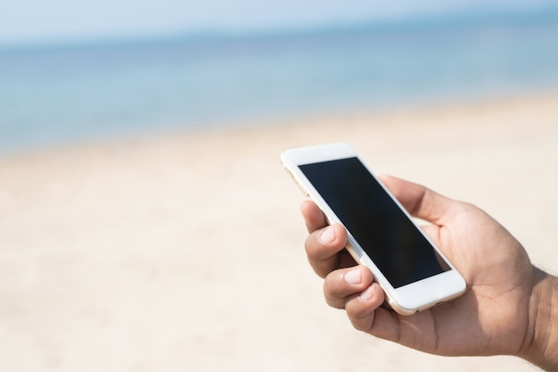 Feche as pessoas homem de mão segurando o telefone inteligente móvel branco na praia com a tela em branco vazia. espaço vazio para o texto. conceito de tecnologia e viagens de férias