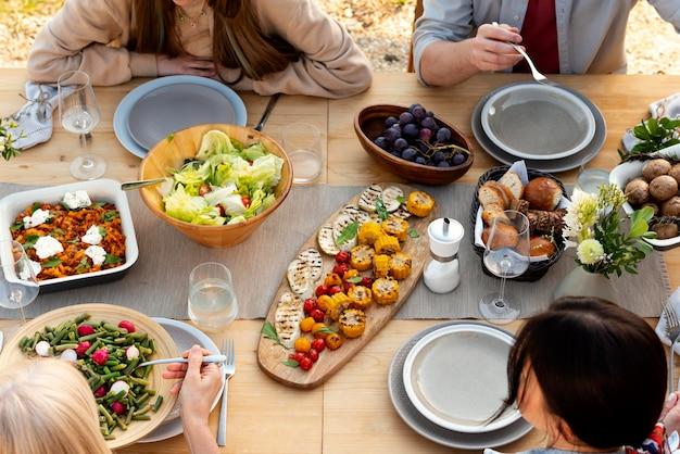 Feche as pessoas na mesa com a comida