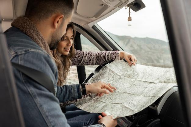 Feche as pessoas no carro com o mapa