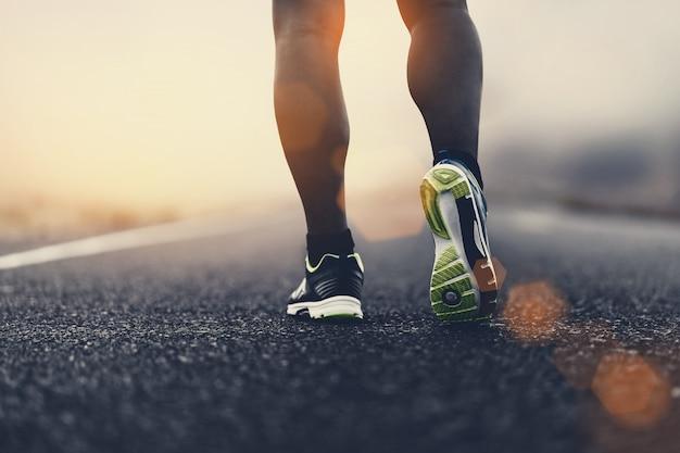 Feche as sapatas do esporte de um corredor na estrada para estilo de vida saudável fitness.