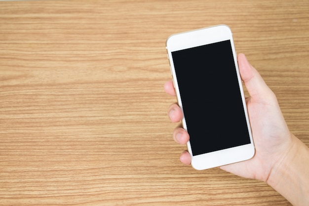 Feche até a mão segurando o celular na velha mesa de madeira na sala.