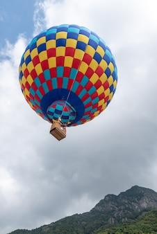 Feche balões de ar quente com manchas vermelhas, amarelas e azuis na montanha