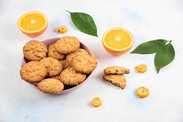 Feche biscoitos caseiros frescos de foto em uma tigela e laranjas orgânicas no solo com folhas.