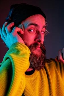 Feche, calma. retrato do homem caucasiano em fundo gradiente de estúdio em luz de néon. lindo modelo masculino com estilo hippie em fones de ouvido. conceito de emoções humanas, expressão facial, vendas, anúncio.