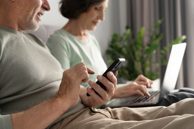 Feche casal sênior com dispositivos