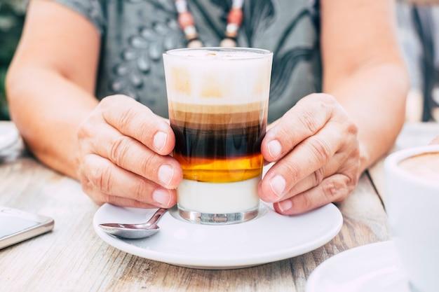 Feche com mãos femininas envelhecidas segurando uma xícara de café multicolorido no café da manhã no bar - mesa de madeira e imagem brilhante - bebida e conceito de bebida para as pessoas