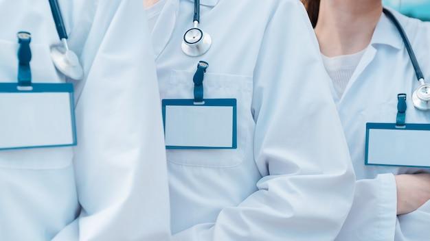 Feche crachás em branco no peito de um grupo de médicos