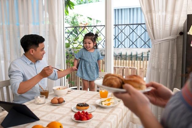 Feche criança e pais na mesa