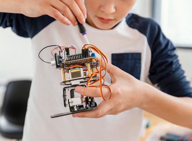 Feche criança fazendo robôs