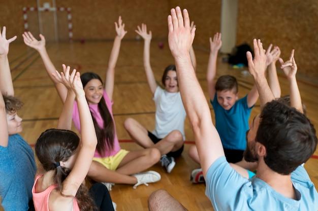 Feche crianças e professor de educação física