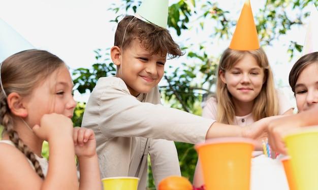 Feche crianças sorridentes comemorando com xícaras