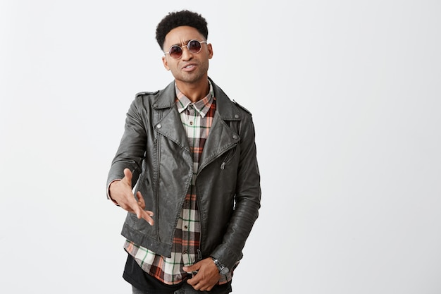 Feche de agressivo jovem bonito de pele escura com penteado afro na jaqueta de couro e óculos gesticulando com as mãos, tendo batalhas de rap com um amigo na festa.