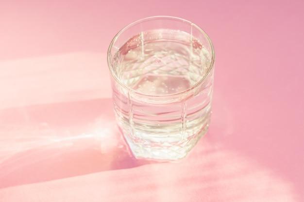 Feche de água com gás em vidro transparente e brilho do sol no fundo rosa.