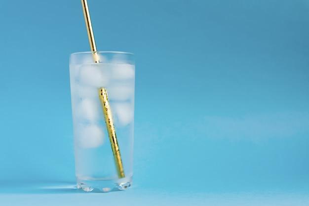 Feche de água pura com gelo e palha de papel dourado em vidro transparente alto e brilho do sol. copie o espaço