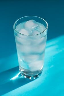 Feche de água pura com gelo e palha de papel em vidro transparente e brilho do sol.