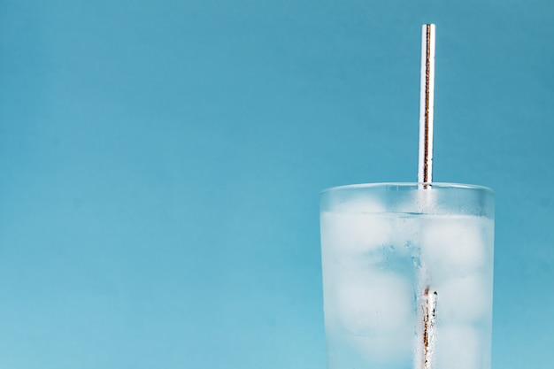 Feche de água pura com gelo e palha de papel prateado em vidro transparente alto e brilho do sol. copie o espaço