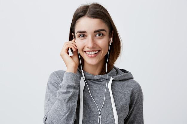 Feche de alegre caucasiana atraente morena jovem com capuz cinza casual, sorrindo brilhantemente, segurando o fone de ouvido com a mão, com a expressão do rosto feliz e relaxado.