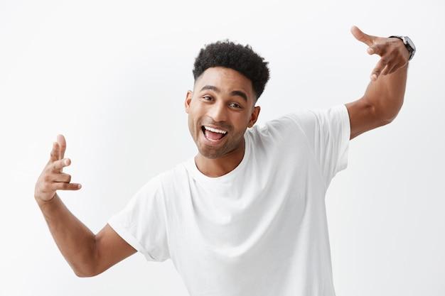 Feche de alegre e alegre homem africano bonito de pele escura com cabelos cacheados em t-shirt branca rindo, gesticulando com a mão, olhando na câmera com expressão alegre e feliz.
