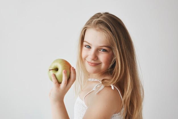 Feche de alegre pequena garota de cabelos claros com olhos azuis em vestido branco, segurando a maçã na mão, sorrindo brilhantemente.