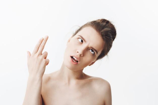 Feche de atraente jovem estudante europeu magro com cabelos escuros na penteado coque e ombros nus, cortando os olhos, fazendo a arma com a mão, mostrando que ela está morta após um longo dia de trabalho.