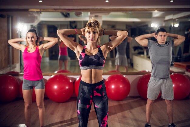 Feche de atraentes focados e motivados jovens fitness pessoas no sportswear em pé e segurando as mãos atrás do pescoço no ginásio.