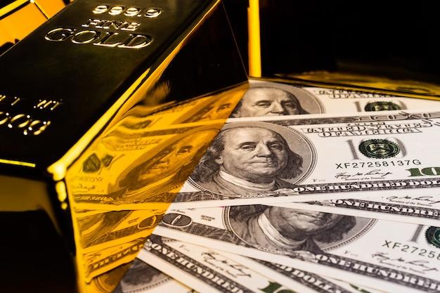 Feche de barras de ouro e notas. conceito financeiro