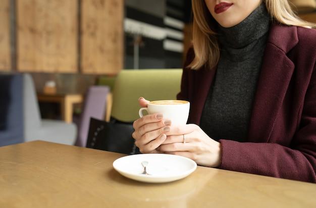 Feche de belas mãos femininas segurando uma xícara branca de café cappuccino.