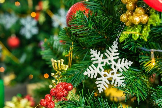 Feche de bolas coloridas na árvore de natal verde, decoração durante o natal e ano novo.