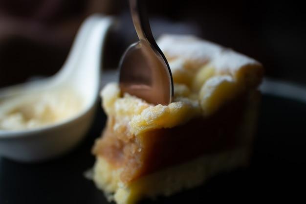 Feche de bolo de maçã crumble com creme na mesa escura no café.