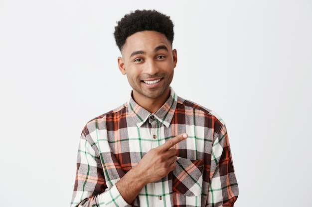 Feche de bonito alegre homem de pele bronzeada com penteado afro na camisa quadriculada casual, sorrindo brilhantemente, apontando de lado com o dedo indicador o parede branca. copie o espaço