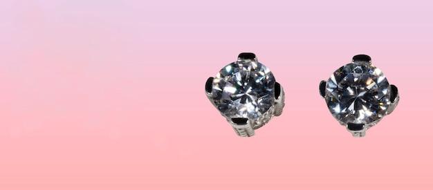 Feche de brincos de diamante em um espaço de fundo rosa para seu texto