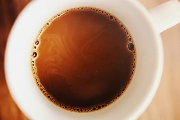Feche de café fresco da manhã arábica na caneca sobre uma mesa.