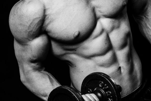Feche de cara musculoso fisiculturista fazendo exercícios com halteres pesos sobre parede preta isolada. preto e branco