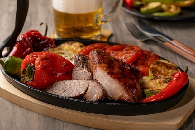 Feche de carne grelhada na panela de ferro fundido com legumes grelhados na mesa de madeira rústica.