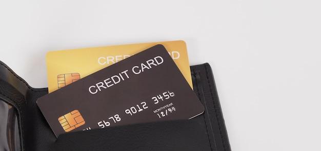 Feche de cartão de crédito preto e cor de ouro em preto na carteira, isolado no fundo branco.