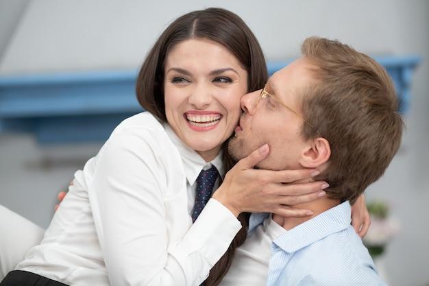 Feche de casal feliz em casa. senhora lindo sorrindo ao ser beijada pelo homem. homem de óculos claros beijando sua linda esposa na bochecha suavemente enquanto ela ri