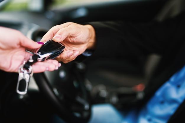 Feche de chaves do carro nas mãos.