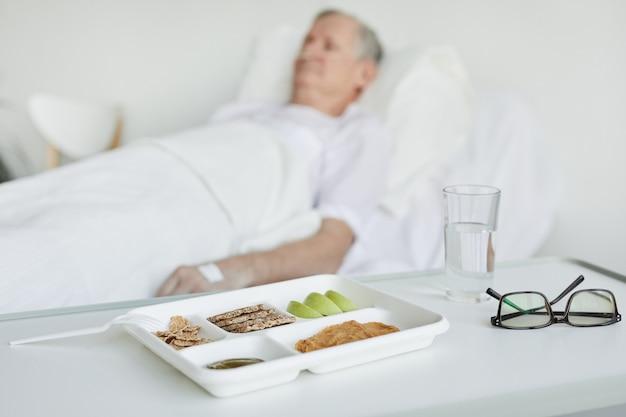 Feche de comida de hospital saudável na bandeja com o paciente no fundo, copie o espaço
